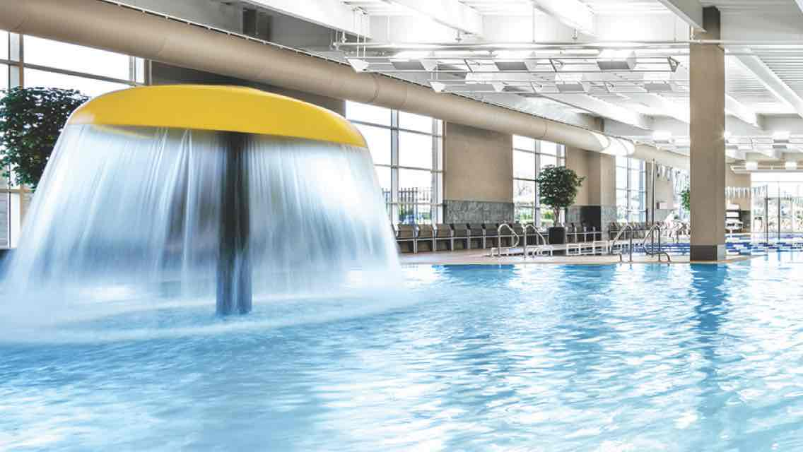 A brightly lit indoor pool featuring a yellow mushroom fountain with flowing water