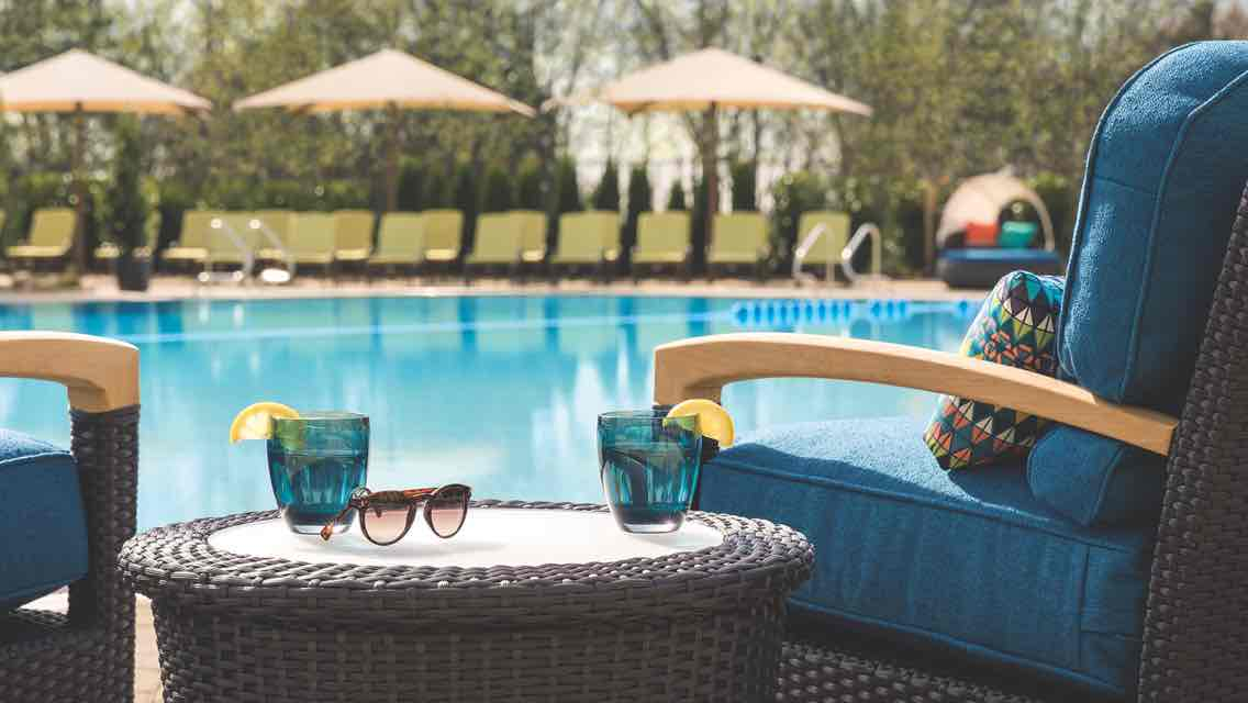 Two lounge chairs and a table with two drink glasses and a pair of sunglasses beside an outdoor leisure pool