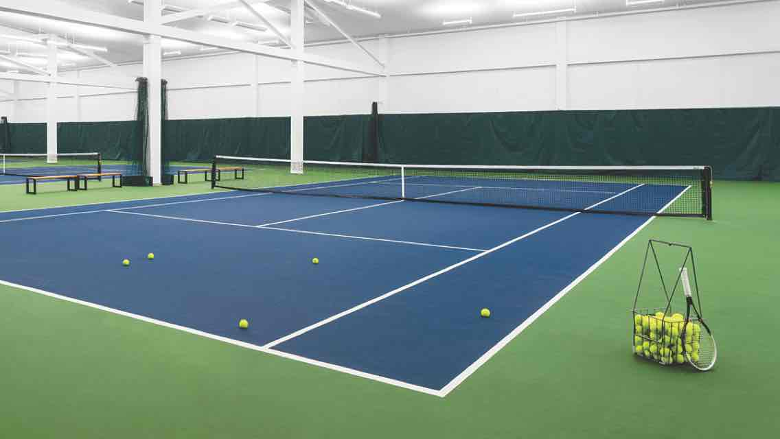A row of indoor tennis courts with a racquet and basket of tennis balls standing by