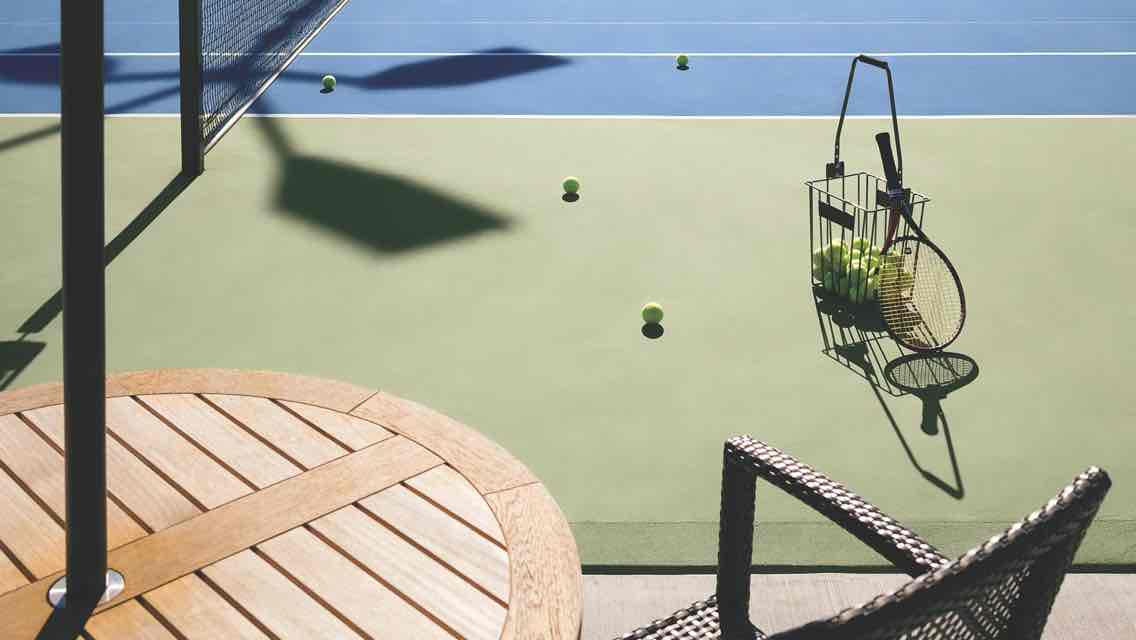A table and chair overlook an outdoor tennis court with a basket of tennis balls and racquet standing by
