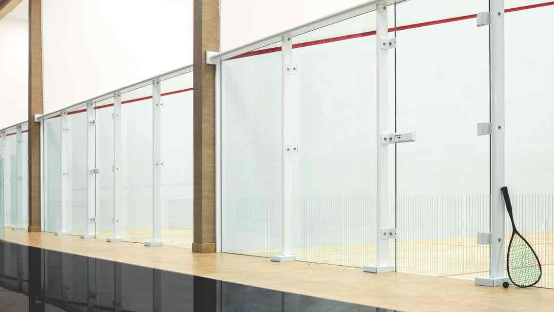"A line of glass-enclosed squash courts behind a reception desk with a sign reading ""Life Time Squash"""