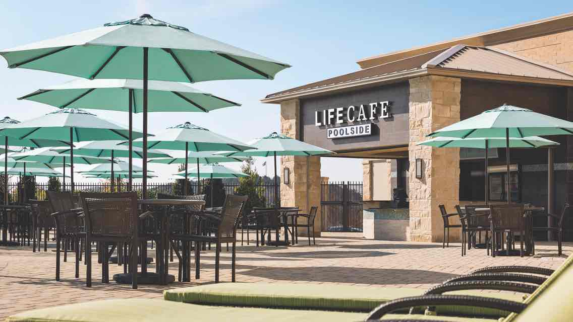 An outdoor Life Time LifeCafe surrounded by umbrella-covered outdoor tables and chairs