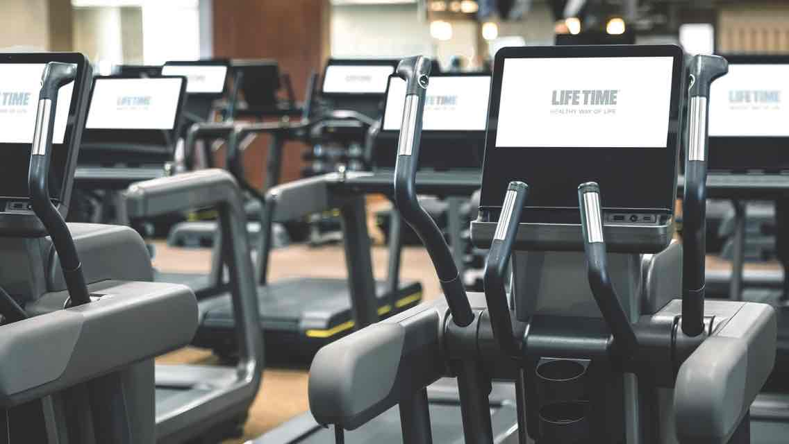 A row of state-of-the art cardio machines on a gleaming wood fitness floor
