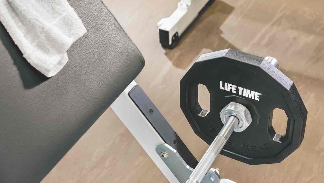 A weighted Life Time barbell and a white towel sit on a padded weight bench with a gleaming wooden fitness floor