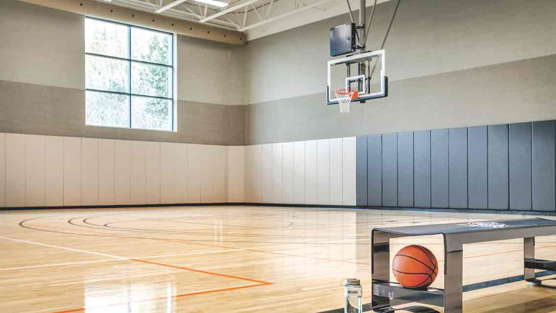 A spacious gym with large windows, a gleaming wood floor, basketball hoops and a cart filled with basketballs