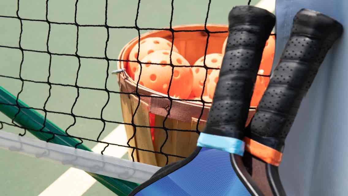 A close-up view of a pickleball net, two pickleball rackets and a wooden basket of orange pickleballs