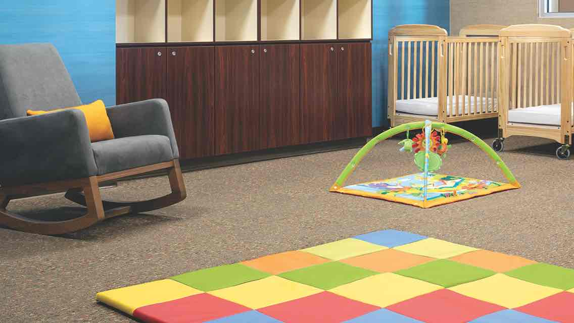 A carpeted infant room with a cushioned rocking chair, a row of wooden cabinets and cubbies, play floormat, an infant play mobile and two wooden cribs