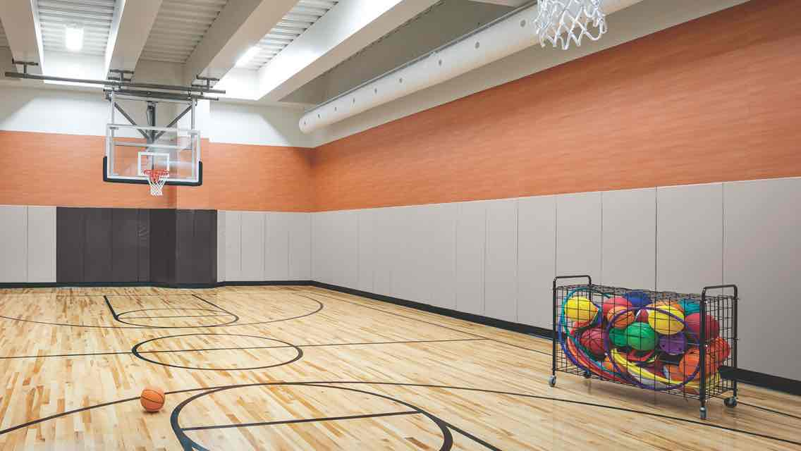 A spacious gym with a gleaming wood floor, basketball hoops and a cart filled with basketballs