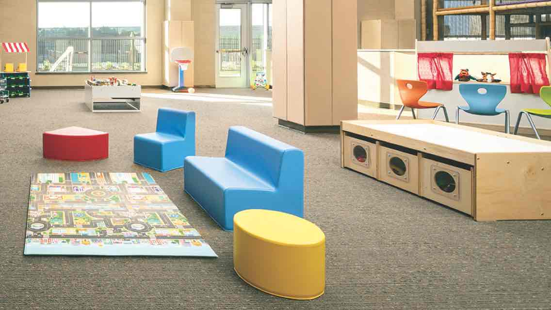 A spacious, sunlit carpeted kids play area with child seating and wooden toy containers