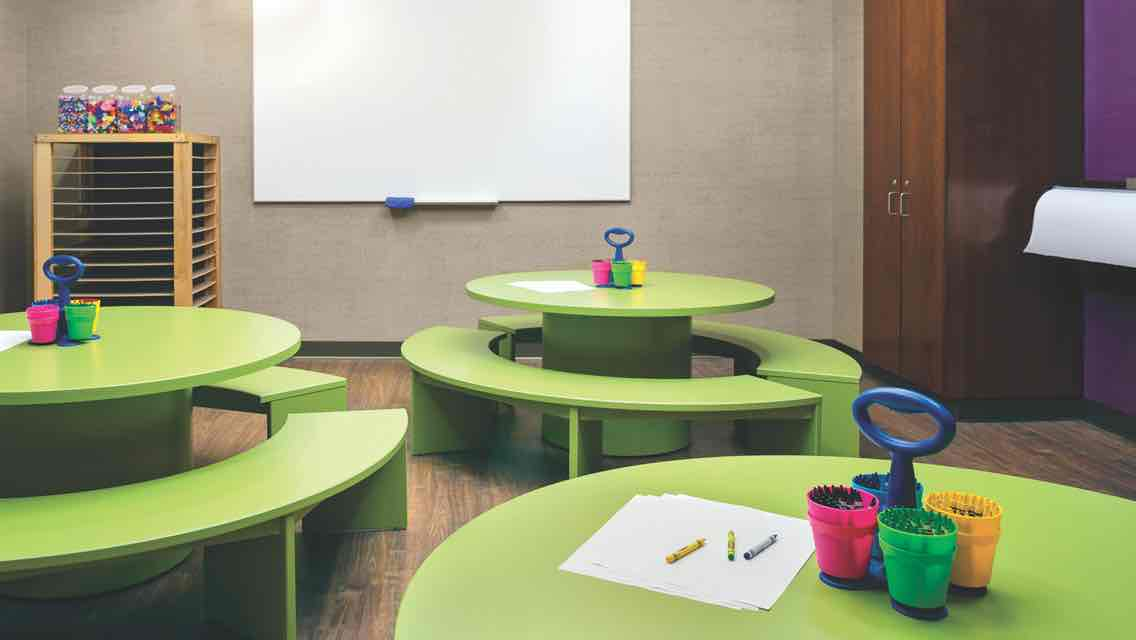 A children's language arts studio equipped with three green tables surrounded by bench seating with containers of crayons and paper