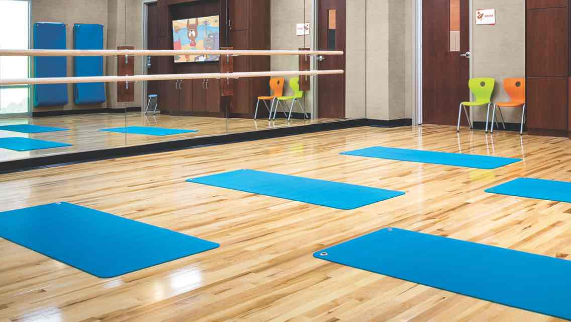 Five blue yoga lined up on the wood floor of a light-filled studio