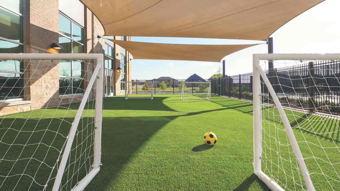 A outdoor play area with a green turf field, two soccer goals lined up and a yellow and black soccer ball