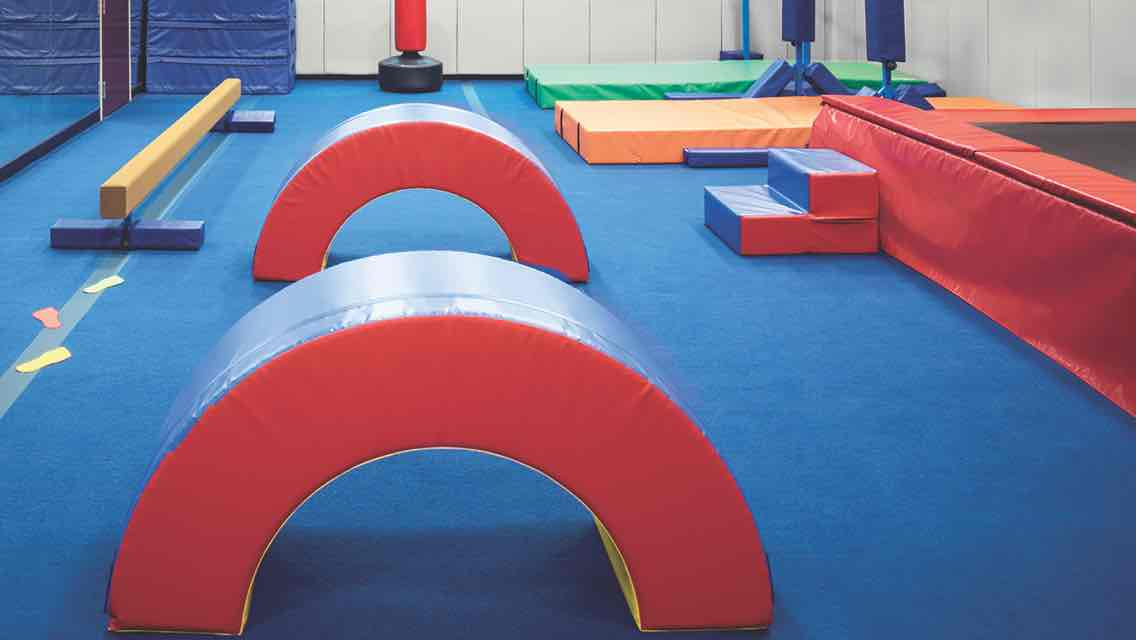 A padded tumbling studio with padded mats, blocks and a balance beam