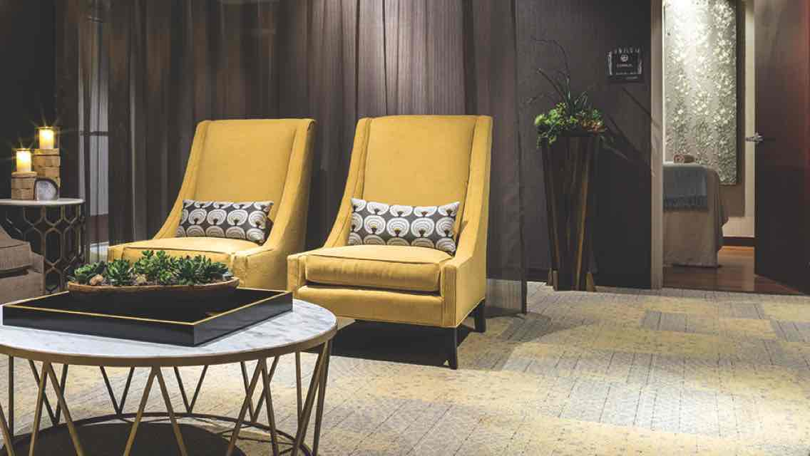 A luxe, candle-lit spa waiting area with cushioned yellow arm chairs, lush carpeting and green plants