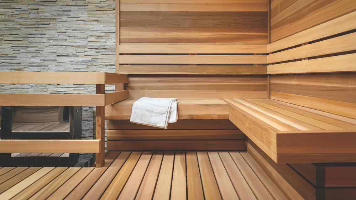 : A pristine sauna with tile walls, wood floors and a wood bench holding a crisp white towel