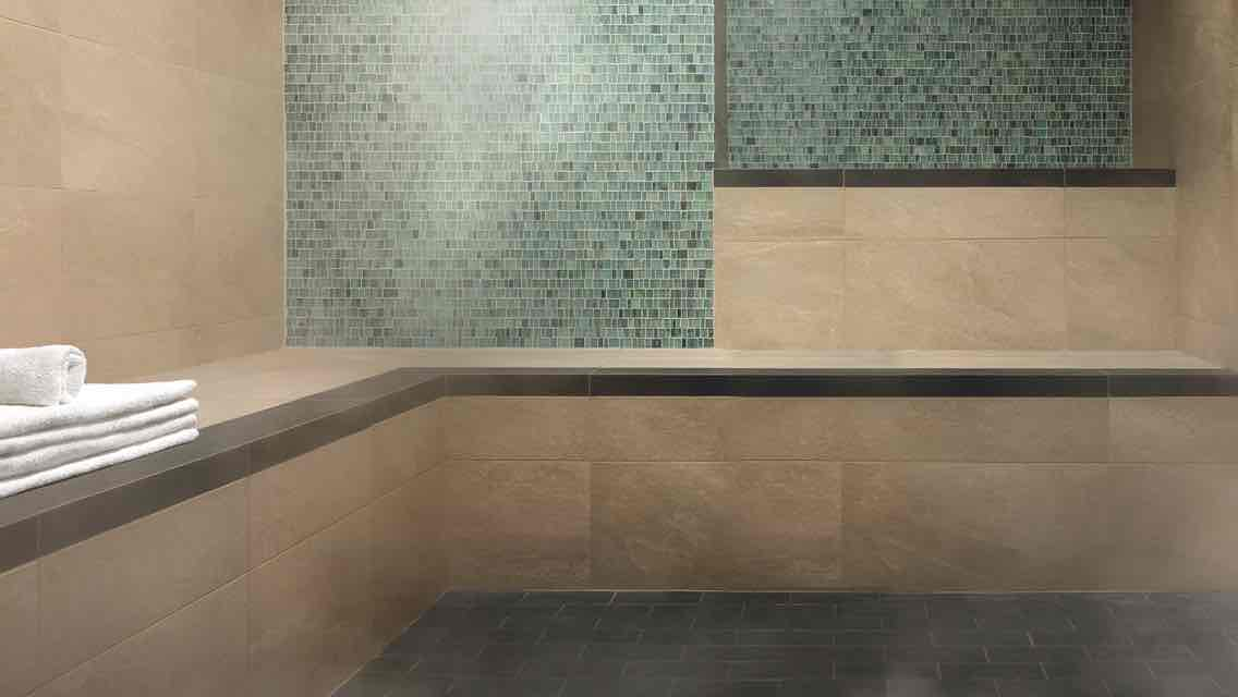 A luxurious, tile-lined steam room with a stack of white towels at the ready