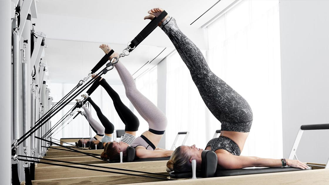 Five women in a Pilates class lying on their backs with their legs in the air on Pilates machines