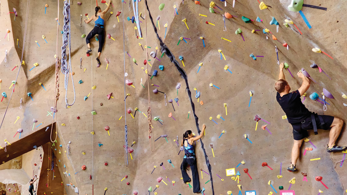3 people half way up a climb wall