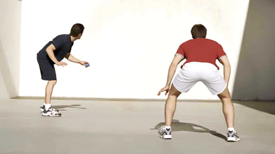 Two men face a wall on a handball court and prepare to start a handball match