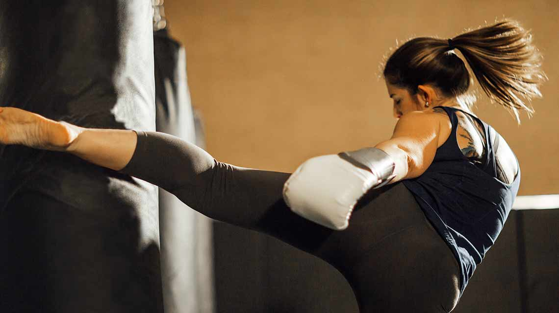 A woman with boxing gloves on, doing a high side kick at a boxing bag