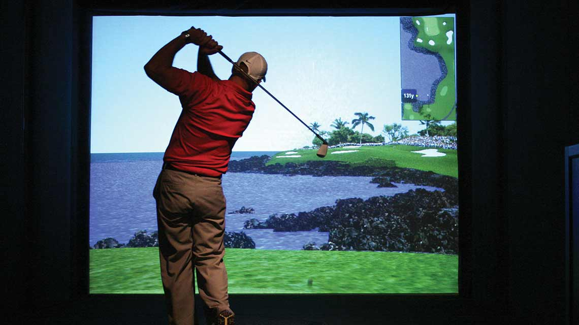 A man swings a golf club behind his back while overlooking a video simulation of grass, trees and water
