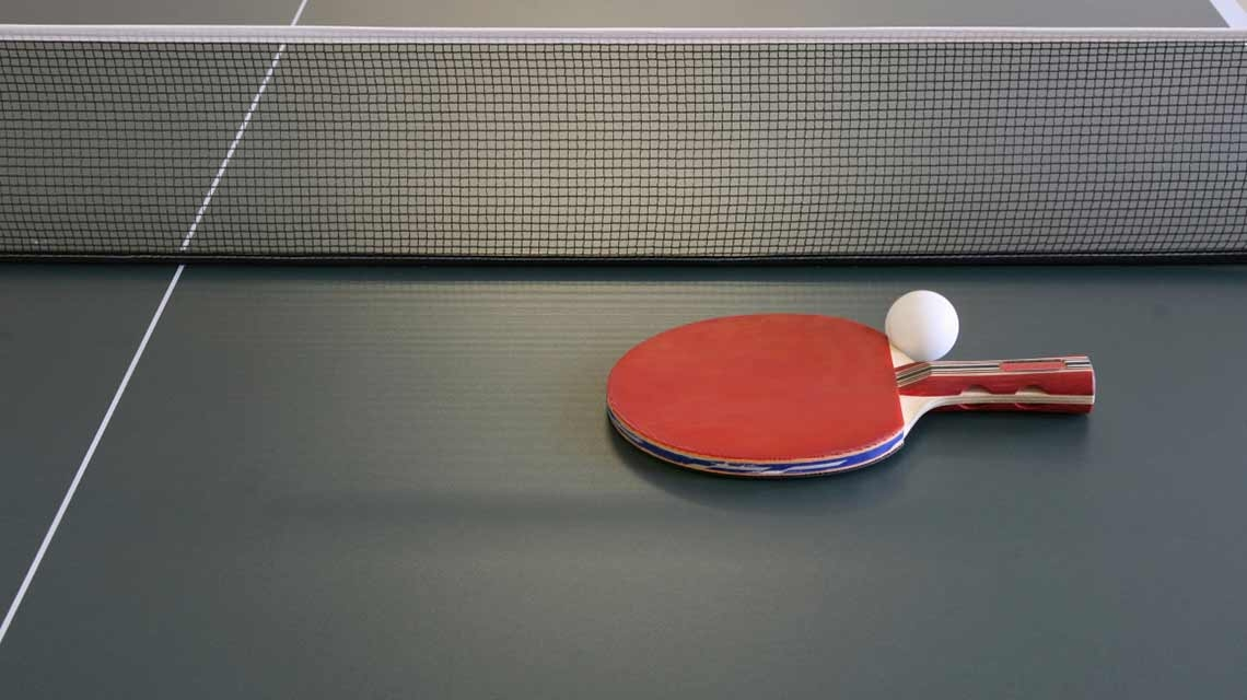 A table tennis paddle and ping pong ball sit atop a table tennis table