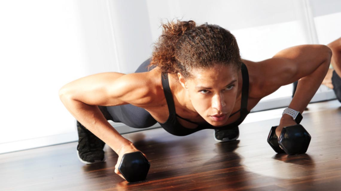 A woman holding dumbbells in a plank position for a studio class