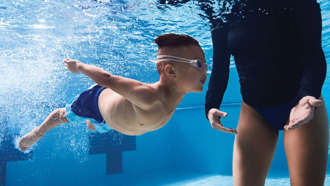 A woman guides a child wearing swim goggles through the pool water