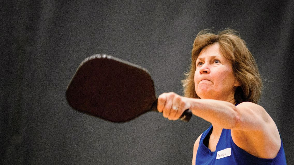A woman in a blue tank top swings a pickleball paddle with her left hand