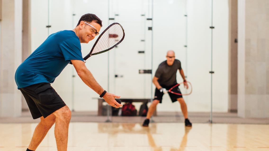 Two men in safety goggles hold racquetball rackets and face each other on the court