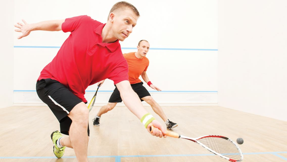 Two men holding squash racquets next to each other while one lunges toward the ball