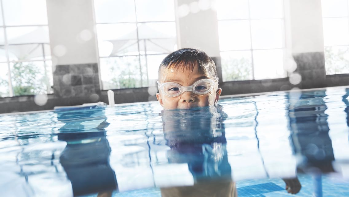 A child wearing swim goggles sticking his head up from underwater