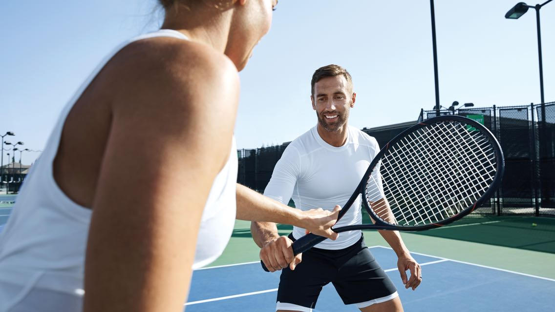 A tennis instructor hands a tennis racquet to a student while they stand on an outdoor court