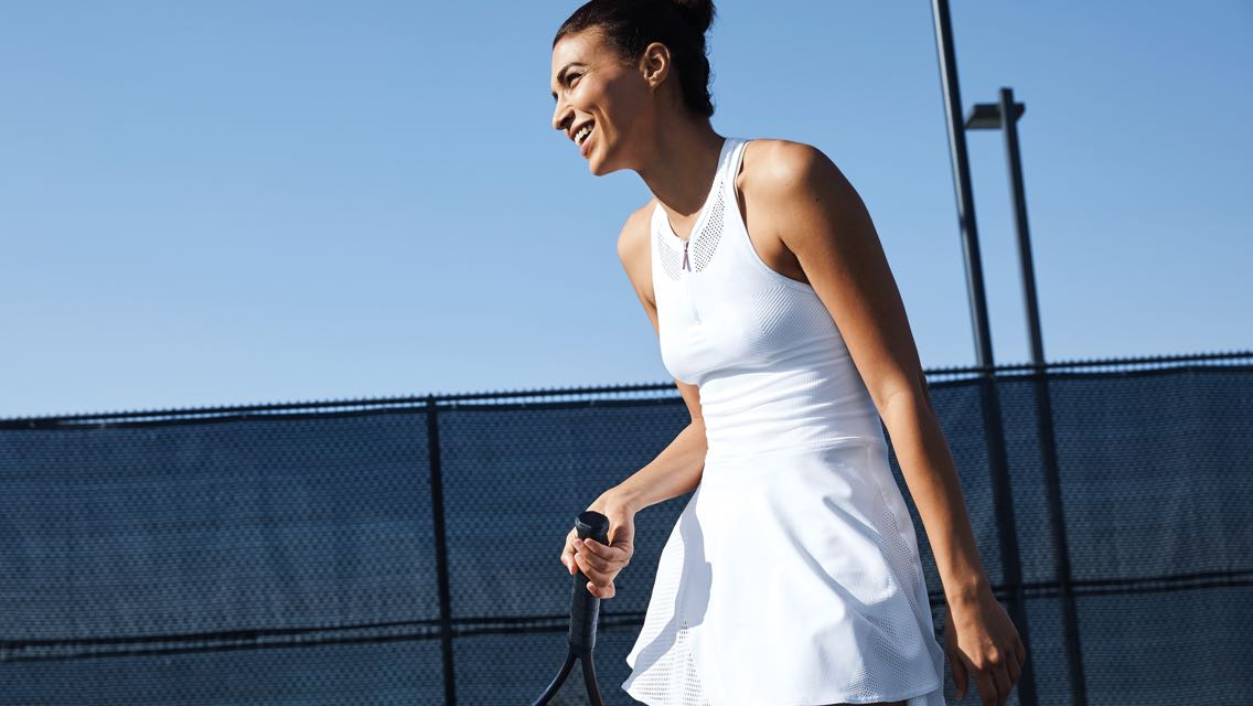 A woman in an all-white tennis outfit holds her racket and smiles while standing on an outdoor tennis court