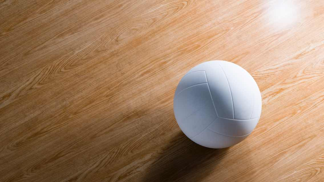 A shiny wooden volleyball court floor and a close-up view of a white volleyball