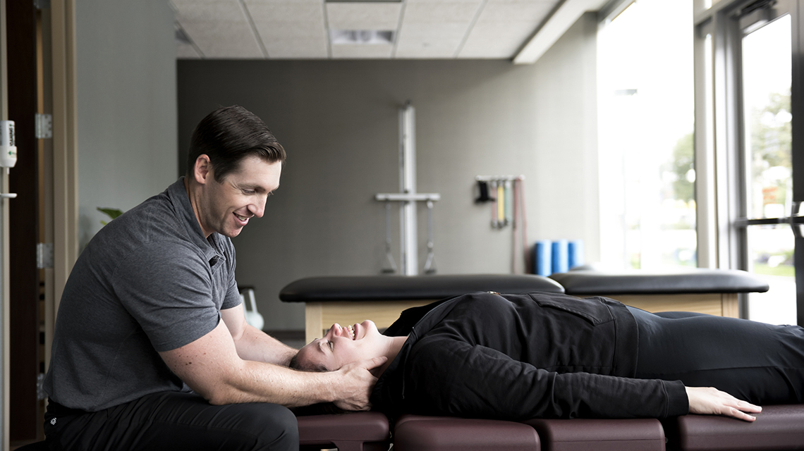 A physical therapist holding the neck of a client who is laying on their back on an adjustment table