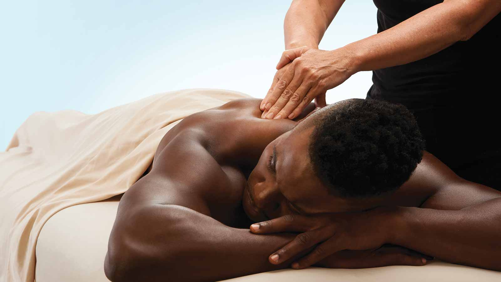 A client covered by a sheet lying face down on a massage table while a massage therapist presses their hands onto his back