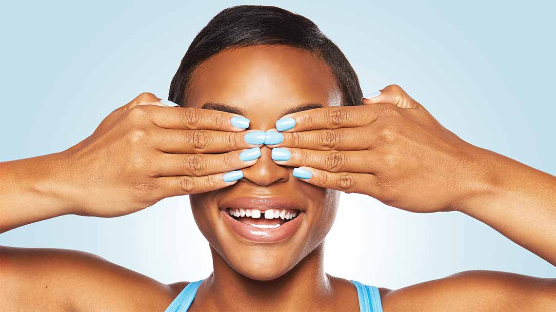 A woman covering her eyes with both hands to showcase her bright blue nail color