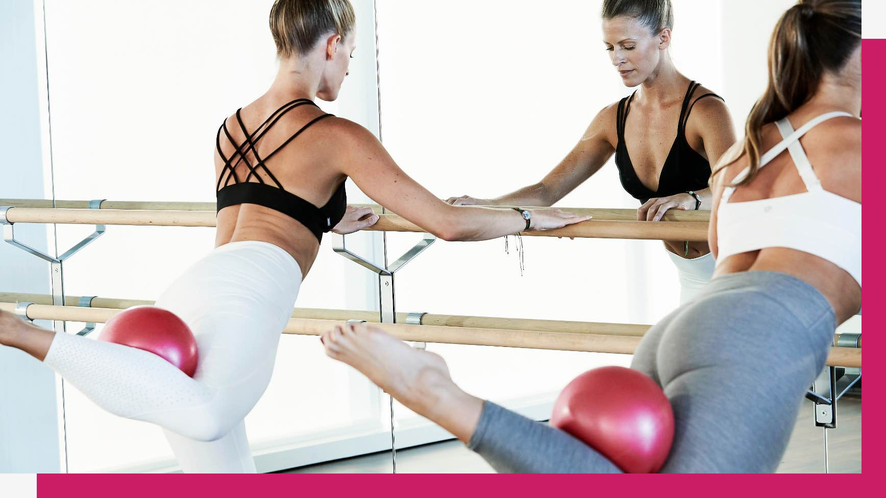 Two women stand facing a mirrored wall holding onto a barre with one leg kicked behind them balancing a red Pilates ball