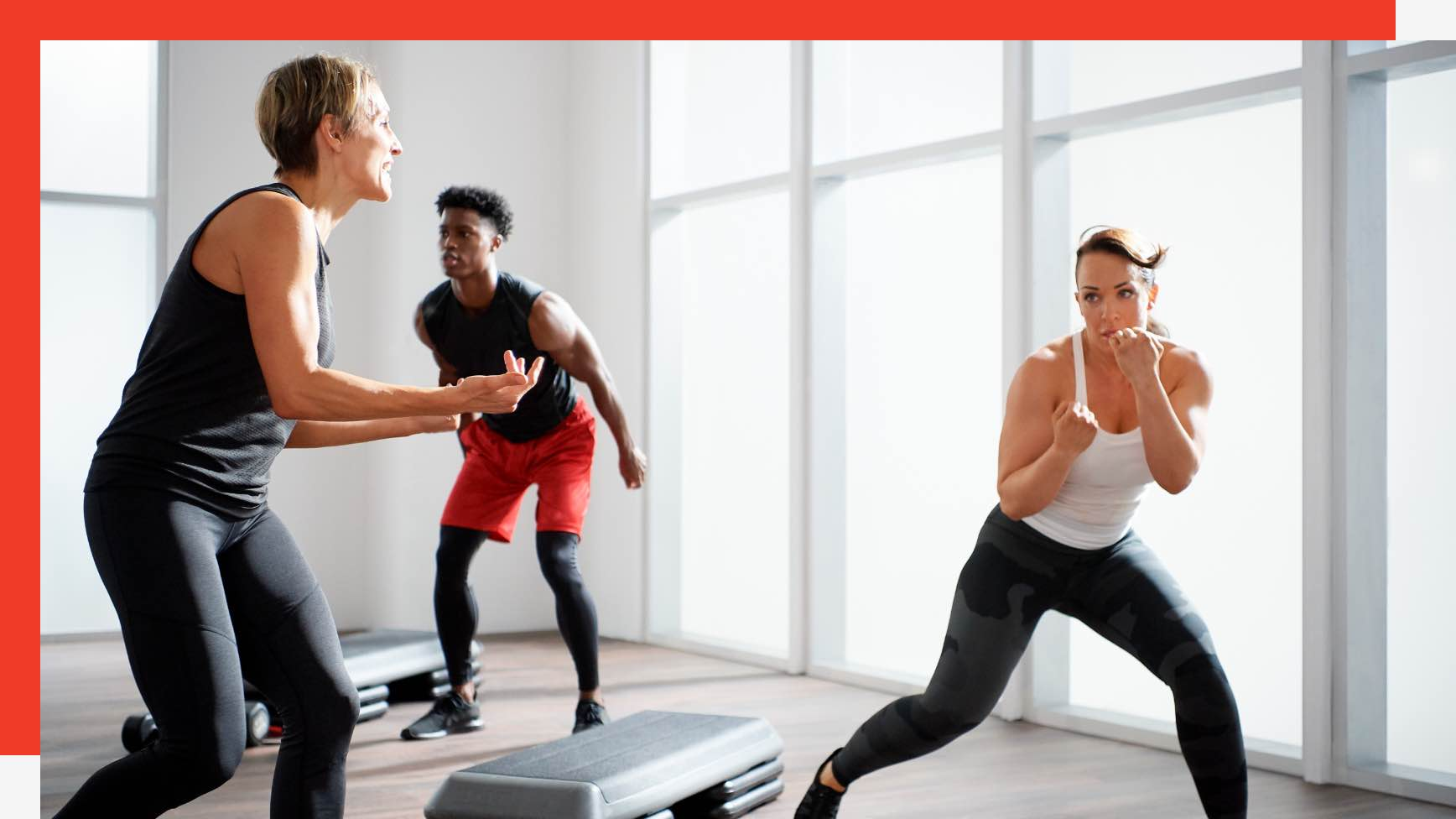 Two people holding boxing hand weights in a group fitness class at Life Time