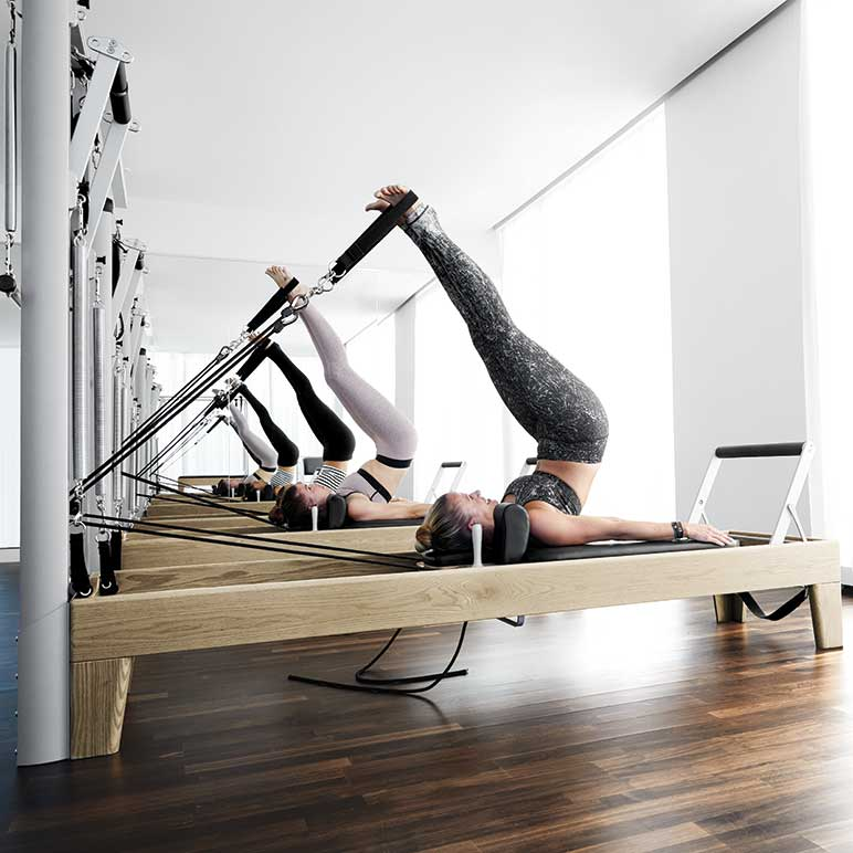 Women participating in a pilates class on Reformers