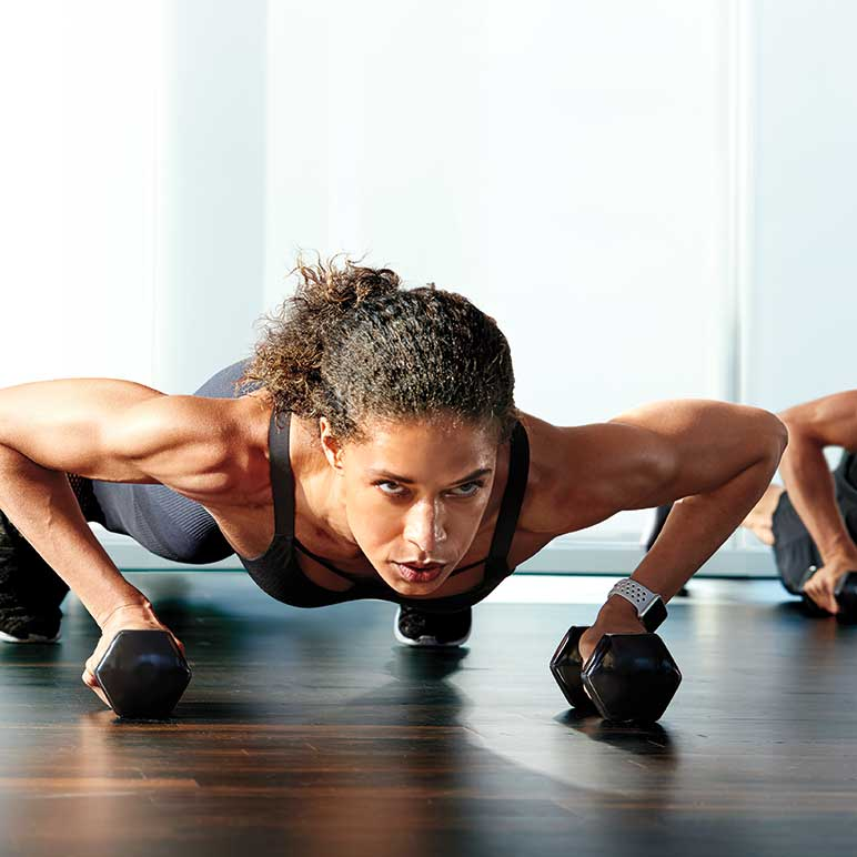 A woman doing push-ups with dumbbells