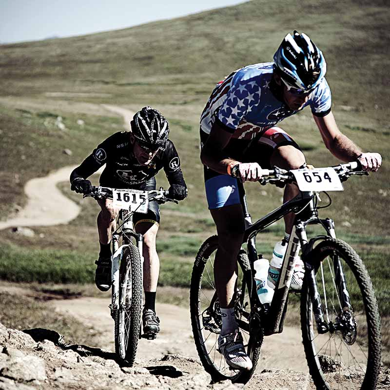 Two men cycling up a rocky path