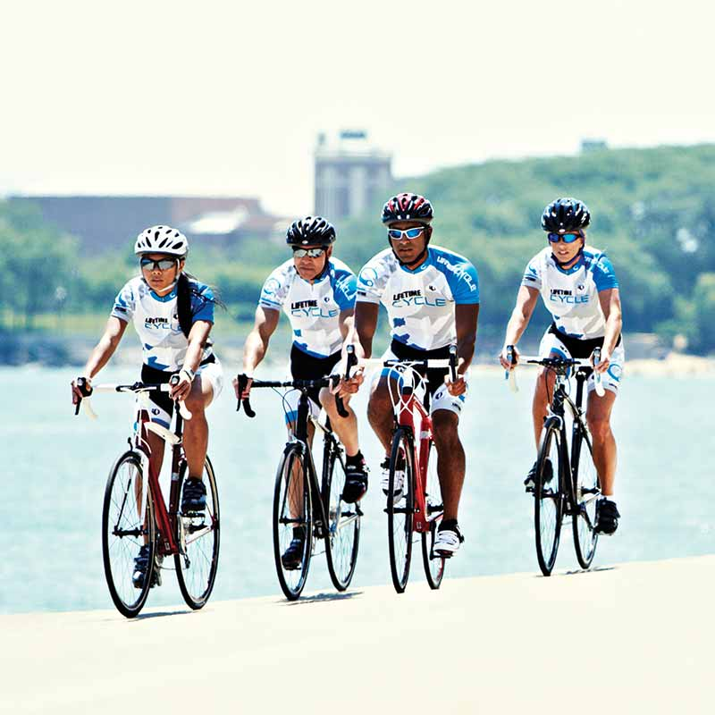 A group of four adults biking & wearing bike apparel