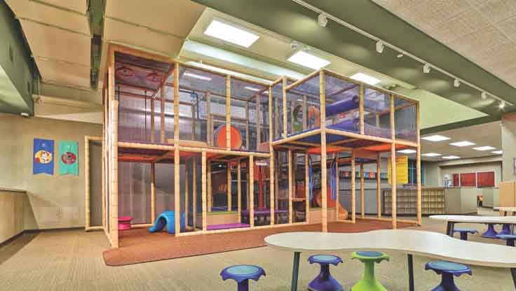 A spacious children's play area with a double-decker climbing structure, tables and colorful stools