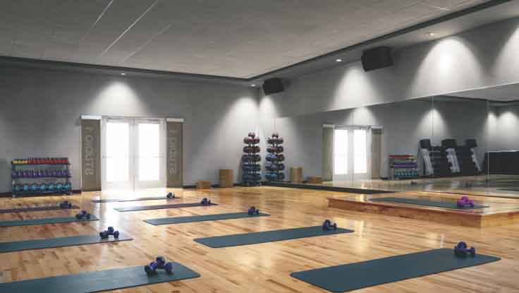 Grey yoga mats, each equipped with a pair of dumbbells, lined up on the gleaming wood floor of a mirrored studio