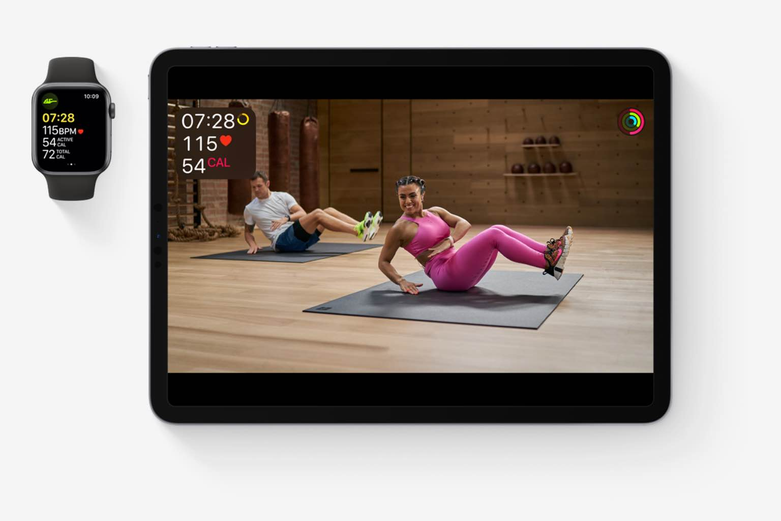 iPad and apple watch with Apple Fitness+ video classes and metrics on the screen.