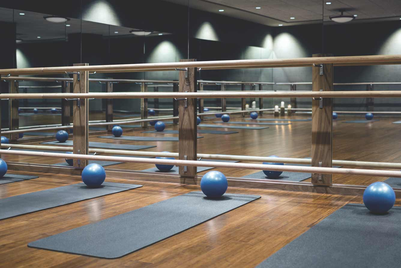 Exercise balls spread out on the wooden floor of a group fitness studio