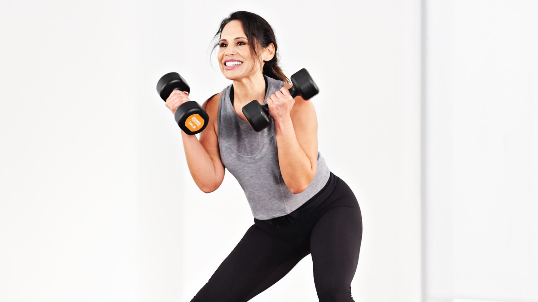A smiling women in workout gear uses dumbbells during a fitness class