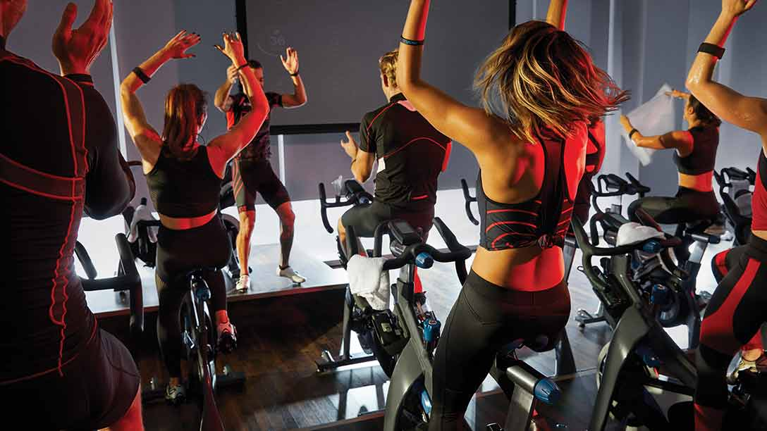 group of cyclists riding bikes together in an indoor cycle class